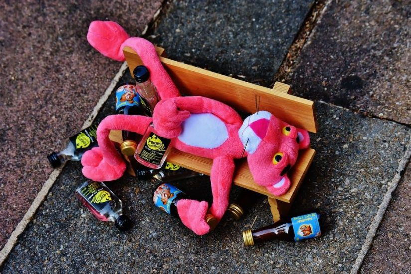 A pink panther doll and liquor bottles